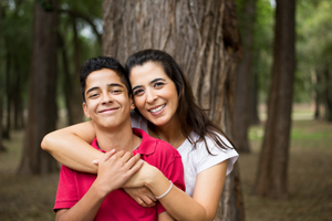 Parenting Teens - Hispanic mother and son smiling with arms around each other