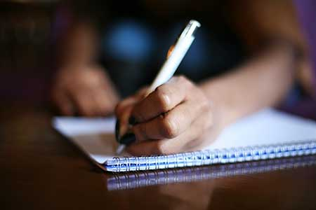hand holding a pen and writing on a pad of paper